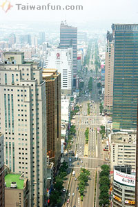 """This is a photo of Taiwan Boulevard, probably the largest street in Taichung. If you look closely on the right side you can see 2 lanes, and then another 2 lane separated by some shrubbery. The separated lane (on the far far right) is designated for scooters. HOWEVER, buses also can use the lane, and cars who plan who turning off of the street. This is what creates being """"between a rock and a hard place."""" There might be a bus on your right who is trying to merge into the left lane, a car on your left, and 3 scooters in front of and behind you. I've only actually been like """"oh shoot, I'm going to be squished like a bug"""" a few times, but it only takes one time to cause unfathomable damage to you and your bike."""