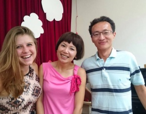 """I also had 6th grade graduation this week. I had to miss Feng Jia's, but at Da Keng's I witnessed them graduate and also sang """"For Good"""" as a part of the ceremony. Afterwards there was a huge feast and lots of chatting. This is me with my coworker Kelly and Brandon."""